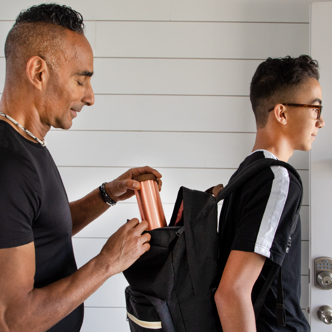 Father putting a Qi Shield EMF protection device in son's backpack