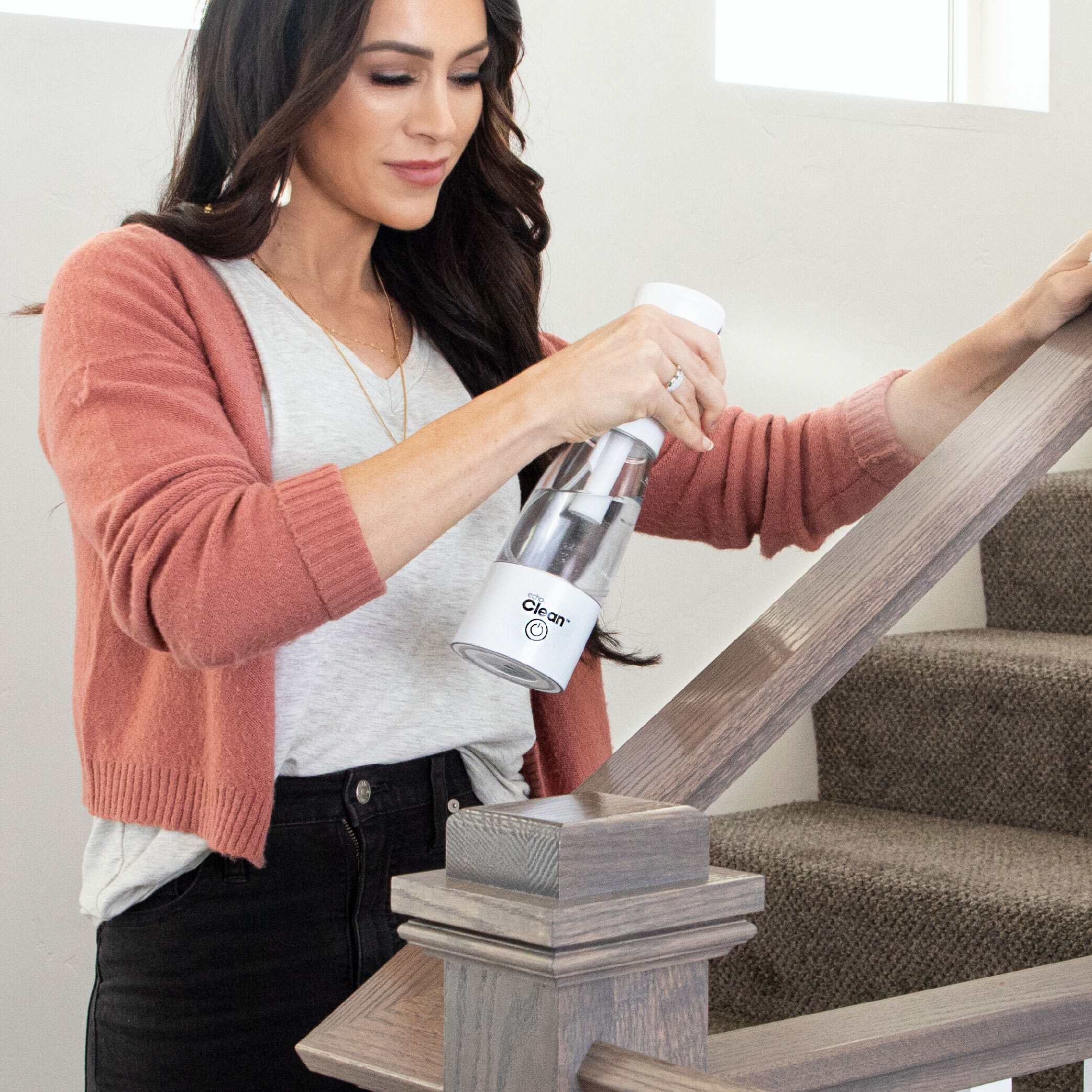 Lady using the Echo Clean all natural cleaner on home stair railing