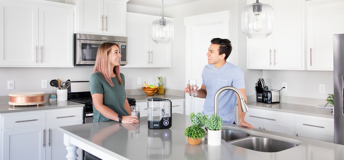 man and woman in kitchen drinking water from Echo H2 Pitcher™
