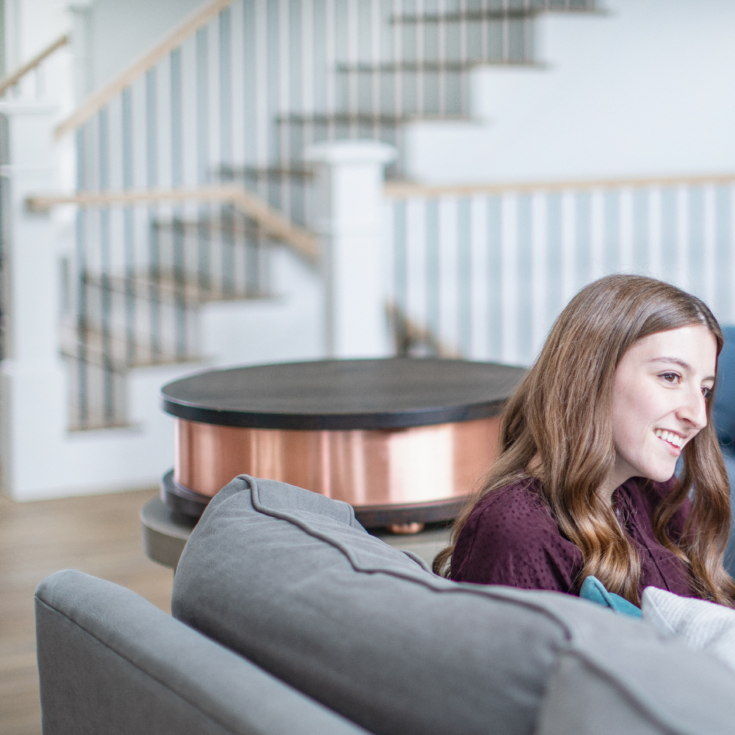 Girl sitting on couch with Qi Home Cell (EMF blocker for home) on table behind her
