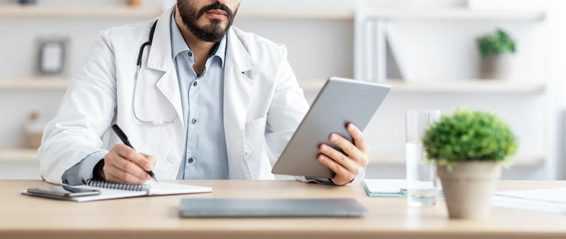 Doctor watching a tablet and writing notes